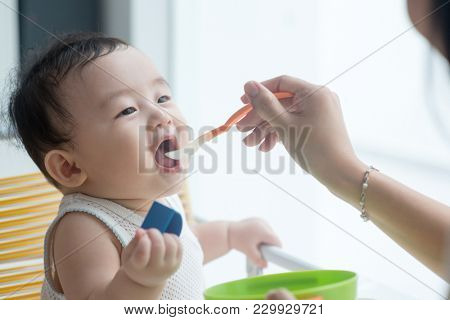 Happy Asian family at home. Mother feeding solid food to 9 months old son in the kitchen, living lifestyle indoors.