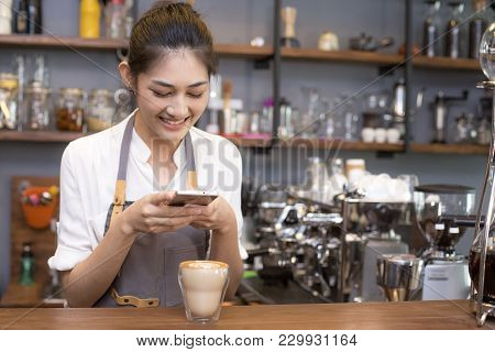 Asian Barista Woman Using Smartphone For Take Coffee Pictures. Woman Using Smartphone With Attractiv
