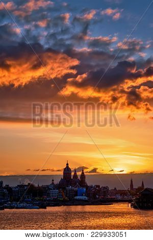 Amsterdam cityscape skyline with  Church of Saint Nicholas (Sint-Nicolaaskerk) on sunset with dramatic sky. Amsterdam, Netherlands