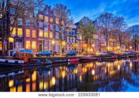 Night view of Amsterdam cityscape with canal, boats and medieval houses in the evening twilight illuminated. Amsterdam,  Netherlands