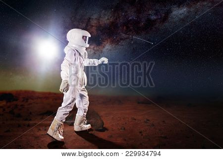 Futuristic Astronaut On The Planet, Standing And Stretches Hand Away