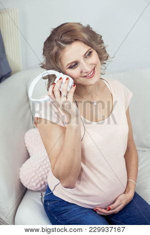 Young Beautiful Pregnant Woman Is Resting At Home. Young Pregnant Woman Listens To Music. Portrait O
