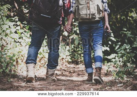 Closeup Image Of A Lover Couple Holding Hands And Trekking In A Tropical Forest Together