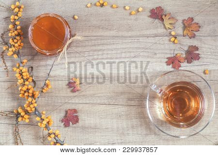 Autumn Healthy Hot Drink Concept. Branch Of Common Sea Buckthorn With Berry, Cup Of Tea, Jar Of Jam