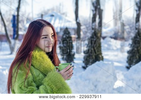 Beautiful Cute Pretty Redhead Female Teenager In A Green Fur Coat Drinking Coffee In The Sunny Winte
