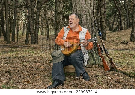 Outdoor Portrait Of Singing Senior Hunter Resting In Evening Forest And Playing Mandolin