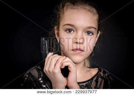 Close-up Portrait Of A Beautiful Young Girl With Gun In Hands Isolated On A Black Background