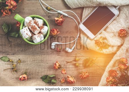 Cup Of Coffee With Marshmallow, White Knitting Wool, Dried Roses Flowers, Mobile Phone And Headphone