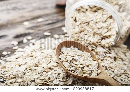 Inverted Can Of Oatmeal On A Wooden Table. The Oatmeal Is Scattered On The Table . Healthy Food For
