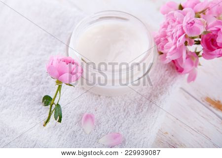 Organic Cosmetic With Rose And Pot Of Moisturizing Face Cream On White Background Top View .