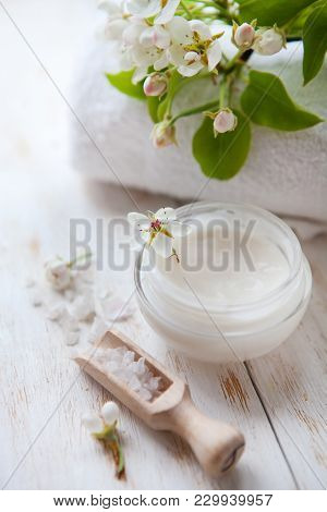 Skin Cream And Beautiful Spring White Flower On White Wooden Table Pot Of Beauty Cream Surrounded By