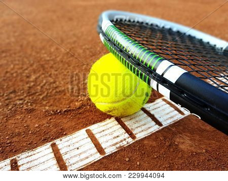 Racket And Tennis Ball On Tennis Court