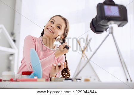 Great Mood. Adorable Cheerful Pre-teen Girl Applying Powder To Her Cheeks And Posing For The Camera