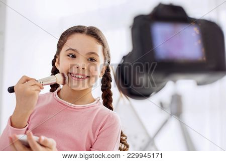Cheerful Mood. Pleasant Upbeat Girl Smiling Happily And Applying Powder To Her Cheek While Filming A