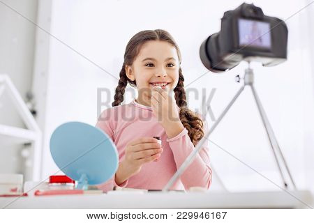 Lip Care. Beautiful Pre-teen Girl With Two Braids Filming A Makeup Tutorial And Applying Lip Balm To