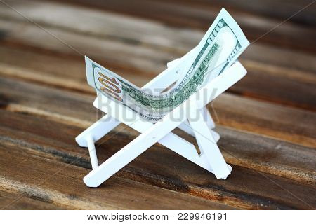 Chaise Long Or Deck Chair Made Of Us Dollar On Wooden Background, Money For Vacation Concept