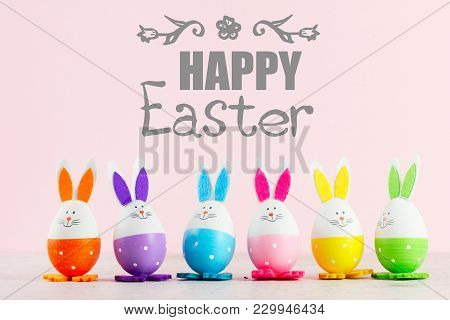 Row Of Funny Easter Bunnies Of Colored Eggs On Pink Background With Happy Easer Greetings