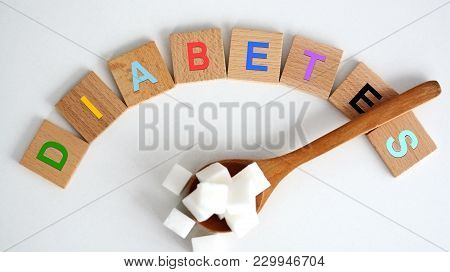 Hyperglycemia Concept With White Refined Sugar Cubes On Wooden Spoon And Colored Letters Spelling Th