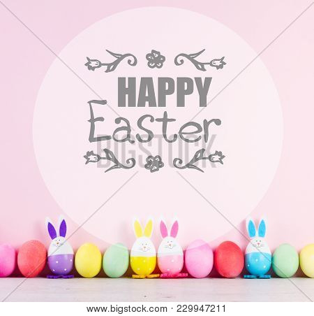Row Of Funny Easter Bunnies And Colored Easter Eggs On Pink Background With Happy Easer Greetings
