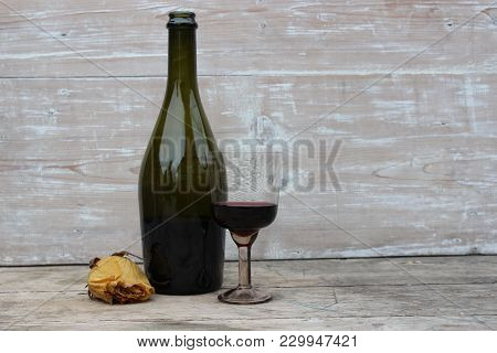 Bottle Of Wine And Glass On The Background Of Wooden Boards