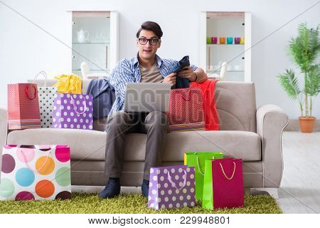 Young man buying clothing online and running blog