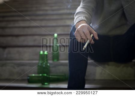 Depressed Man Sit In Underground Road With Beer And Cigarette