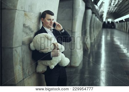 Guy With A Plush Soft Toy Calling On The Phone Congratulating You On The Holiday.