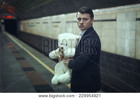 Sad Young Man With A Teddy Bear In His Hands Is Standing At A Subway Station.
