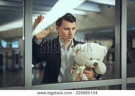 Sad Man With A Toy Bear Waiting For A Meeting. He Looks Out The Window