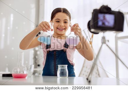 Wannabe Chemist. Cheerful Pre-teen Girl Mixing Holding Two Flasks With Colorful Chemicals And Showin