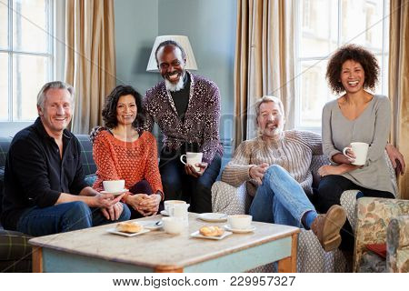 Portrait Of Middle Aged Friends Meeting In Coffee Shop
