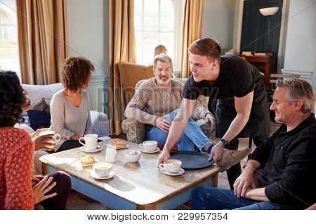 Waiter Serving Group Of Mature Friends In Coffee Shop