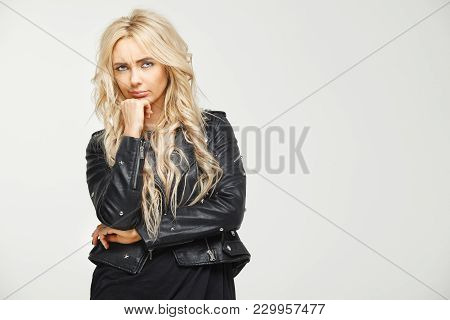 Gorizontal Image Of Young Blond Woman Is Confused With The Distrustful And Frowning Look On Her Face