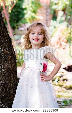 Small Girl Kid With Long Blonde Hair And Pretty Smiling Happy Face In Prom Princess White Dress Stan