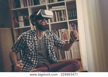 Young Man Enjoying His Leisure Time Playing A Driving Simulation Video Game, Wearing Virtual Reality