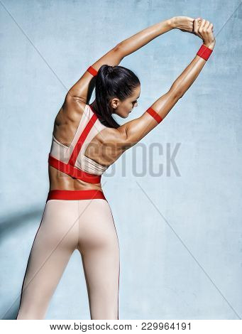 Sporty Young Woman Doing Fitness Exercises For The Warm-up Of The Back On Grey Background. Rear View