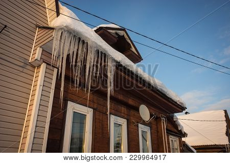 Icy Icicles On  Roof Of Houses In  Russian Winter