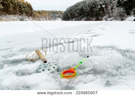Tackles For Winter Fishing, An Ice-picking Device And A Fishing Pole Near The Hole With