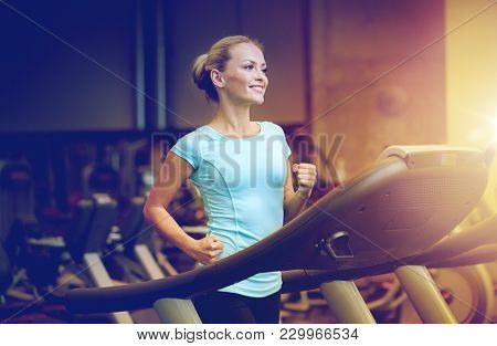 sport, fitness, lifestyle, technology and people concept - smiling woman exercising on treadmill in gym