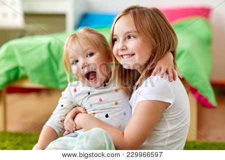 childhood, family, expressions and people concept - happy little girls or sisters hugging at home