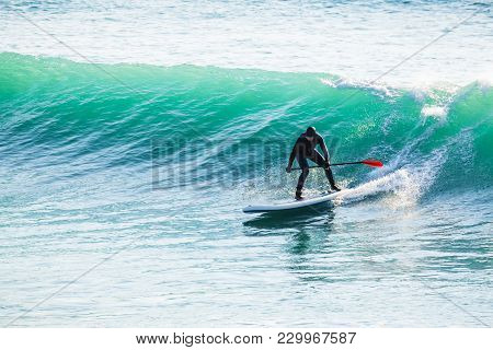 Surfer Ride On Stand Up Paddle Board On Ocean Waves. Stand Up Paddle Boarding In Sea