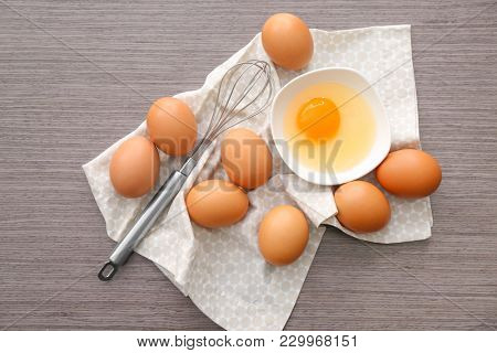 Bowl with chicken egg and whisk on table