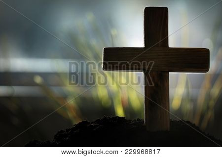 Wooden cemetery cross on blurred background