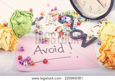 Avoid Word Written On Notepad. Crumple Paper, Clock And Word Block On White Background