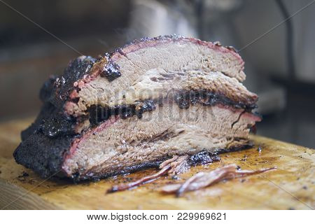 Two Large Pieces Of Smoked Brisket Meat On A Wooden Board, Concept Of Cooking And Haute Cuisine