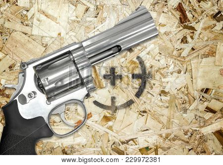 Gun And Target On A Wooden Background.
