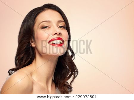 beauty, make up and people concept - happy smiling young woman with red lipstick over beige background