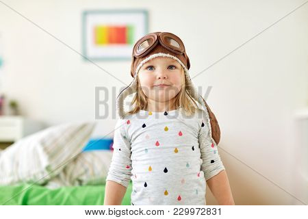 childhood, imagination and dream concept - happy little girl in pilot hat playing game at home
