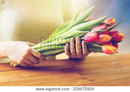 people, holidays and womens day concept - close up of woman holding tulip flowers above wooden table