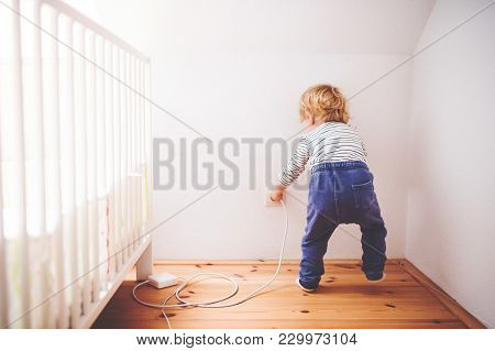Little Toddler Playing With A Plug. Domestic Accident. Dangerous Situation At Home. Rear View.